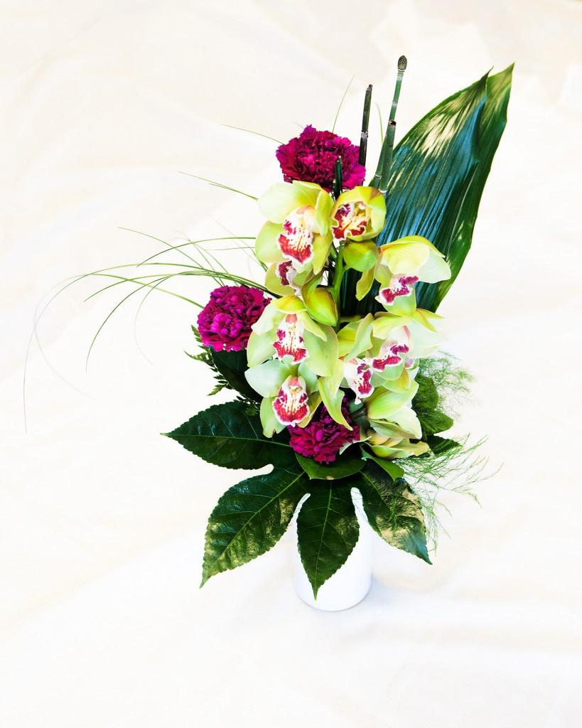 """Reijo Timperin kimpussa on neilikkaa ja orkideaa sekä tuonenkieloa, karhuheinää, parsaa, araliaa ja nahkalehteä. Timperi on mies, joten hänen kimpussaan on käytetty vahvoja värejä. Kimppu on tyyliltään ja muodoiltaan maskuliininen. Sen voisi antaa Timperille missä tahansa tilaisuudessa. """"Värien puolesta kimppu voisi mennä myös suruun, mutta tässä vihreä on kevään väri"""", Turunen sanoo."""